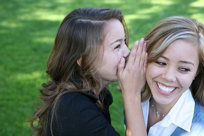 697849-two-teenage-women-telling-secrets-in-the-park